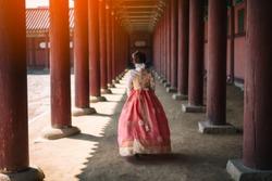 Young asian woman traveler in korean national dress or Hanbok walking traveling into the Gyeongbokgung Palace at Seoul city, South Korea.