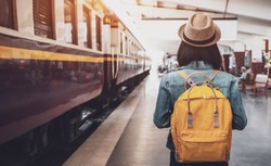 Young asian woman traveler with backpack in the railway, Backpack and hat at the train station with a traveler, Travel concept. Woman traveler tourist walking at train station