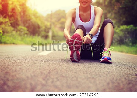 young asian woman tying shoelace   #273167651