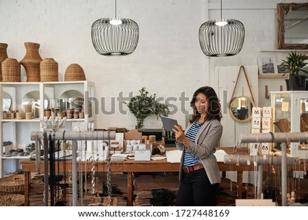 Young Asian woman using a digital tablet while standing by a display in her stylish boutique