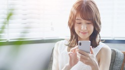 Young asian woman using a smart phone.