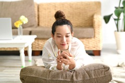 Young asian woman using a smart phone in the living room.