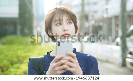Young asian woman using a smart phone on the street. Stock photo ©