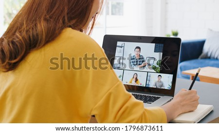 Young Asian woman video call conference, online remote meeting with business coworker, at home. New normal lifestyle, social distancing, internet technology, businesswoman work from home concept