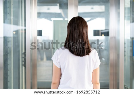 Young Asian woman waiting for the elevator by standing in front of the elevator gate, modern elevator made from glass installing inside the airport hallway.