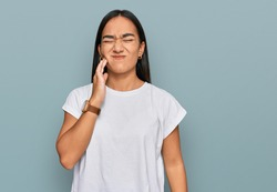 Young asian woman wearing casual white t shirt touching mouth with hand with painful expression because of toothache or dental illness on teeth. dentist