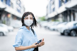 Young Asian woman wearing face mask under face shield, is standing at a domestic street. Concept new normal of commuters after covid-19 epidemic