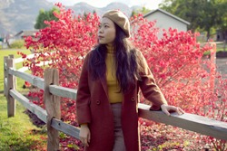 Young Asian Woman Wearing Fall And Autumn Attire Leaning By A Fence