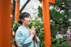 Young asian woman wearing kimono. Prayer in shrine. Japanese traditional clothes.