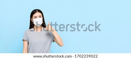 Young Asian woman wearing medical face mask and giving thumbs up isolated on light blue banner background with copy space