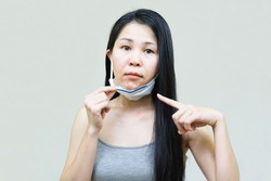 Young asian woman wearing medical face mask  her hand point at pimple on chin,Skin allergy,acne from wearing a mask.