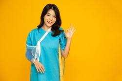 Young Asian woman wearing patient outfits and put on a soft splint due to a broken arm using crutches and showing ok sign isolated on yellow background, Personal accident concept