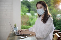 Young Asian woman wearing protective face mask works on a laptop at home office on her holliday. During quarantine of coronavirus pandemic and Anti-coronavirus COVID-19 outbreak protection.