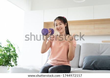 Young asian woman weight training workout exercise and hand thumb up at home, self care fitness body development concept