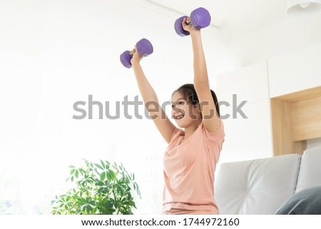 Young asian woman weight training workout exercise by dumbbell hand rise up over head at home, self care fitness body development concept