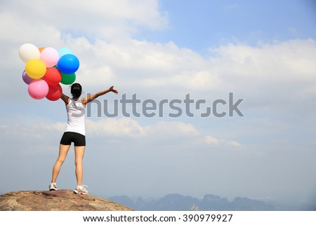 young asian woman with colored balloons on mountain peak #390979927