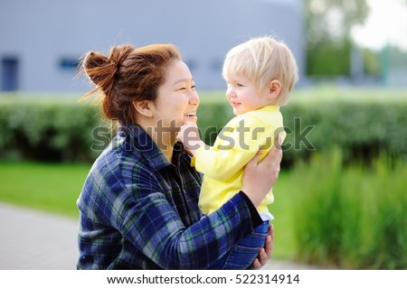 Young asian woman with cute caucasian toddler boy. Babysitting concept #522314914