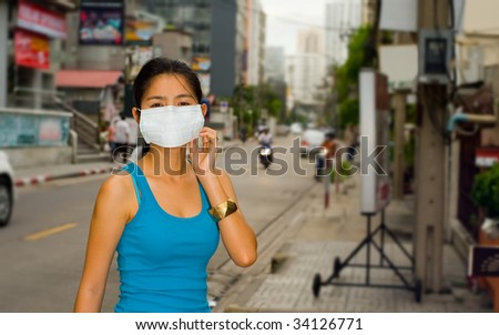young asian woman with face mask in the streets of bangkok - stock photo