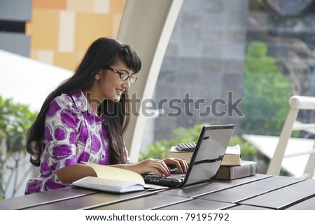 Young asian woman with glasses working outdoor
