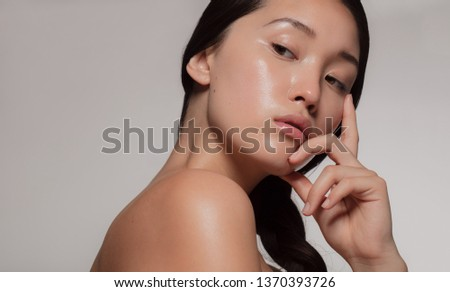 Young asian woman with glowing skin looking away with an attitude. Female with beautiful skin against beige background.