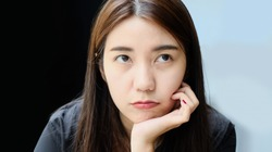 young asian woman with moody angry face while sitting put hand on face. complaint because dissatisfaction expression of brunette Thai lady show under eye dark circle and need treatment