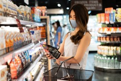 Young Asian woman with protective face mask with shopping cart basket in supermarket inside department store. Asia girl doing grocery and choosing things to buy during Covid-19 coronavirus pandemic.