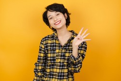 Young asian woman with short hair wearing plaid shirt standing over yellow background showing and pointing up with fingers number four while smiling confident and happy.