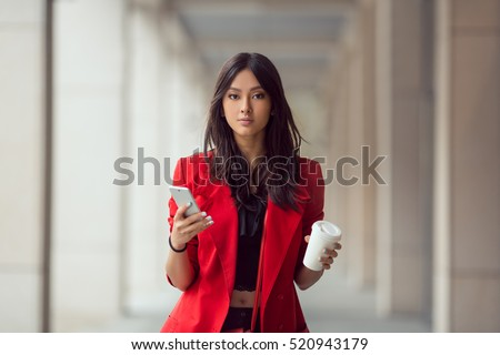 Young Asian woman with smartphone standing against street blurred building background and looking. Fashion business photo of beautiful girl in red casual suite with phone and cup of coffee #520943179