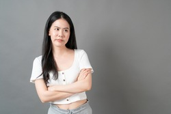 Young asian woman with sulk face in white shirt on grey background