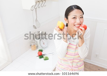 Young Asian woman with vegetables in the kitchen