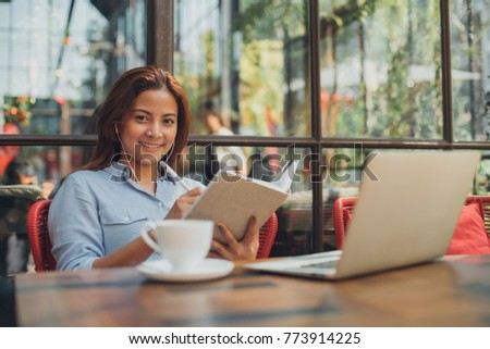 Young Asian woman working with laptop in cafe coffee shop #773914225