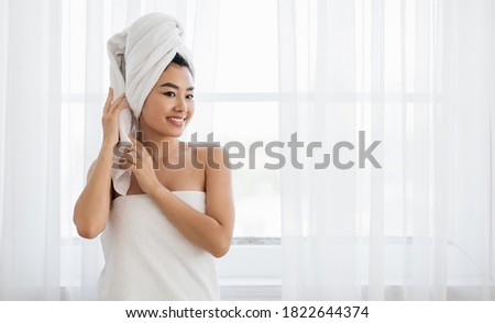 Young asian woman wrapped in towel standing next to window at bedroom, drying her hair after morning shower. Smiling lady with towel on her head looking at empty space, home interior, panorama Stock photo ©