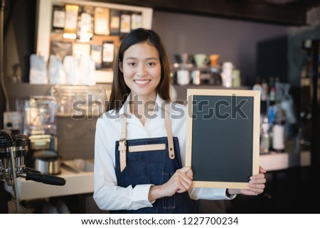 Young asian women barista holding blank chalkboard menu in coffee shop