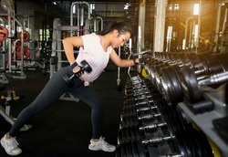 Young asian women training do muscle building exercises using dumbbells.Young fitness woman taking a dumbbell from rack in  gym.Fitness dumbbells, weights equipment,Gym sport fitness concept.