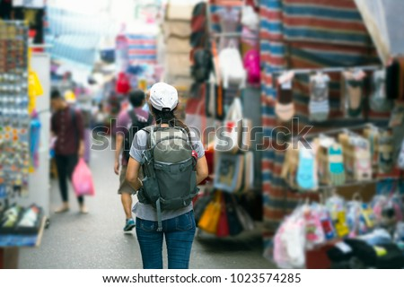 Young Asian women traveler with backpack walking market street vacation, tourism concept traveling on holidays in Hong Kong - Shutterstock ID 1023574285