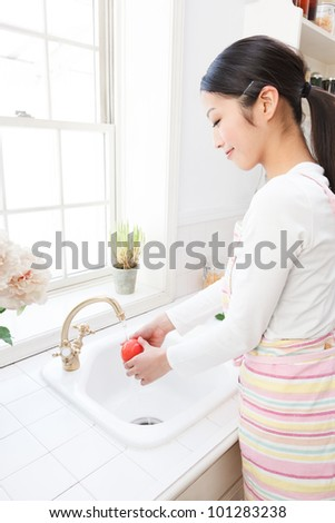 Young Asian women wash the tomatoes in the sink by the window