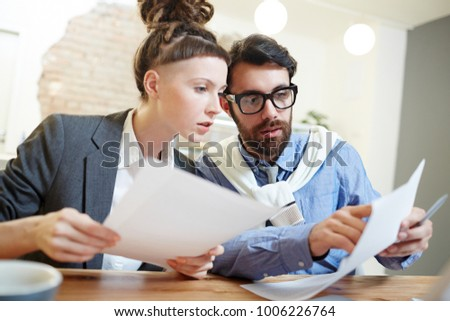 Young associates reading terms of new contract while confident man pointing at one of its points #1006226764