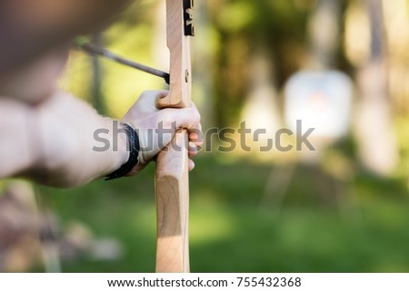 Young Athlete Aiming Arrow At Target Board In Forest