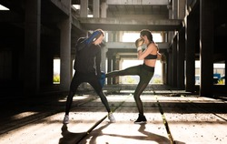 Young athlete couple doing kick boxing exercise in an old abandoned building