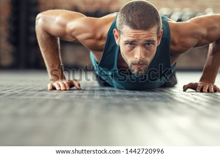 Photo of  Young athlete doing push ups as part of bodybuilding training. Muscular guy doing a pushup on floor at crossfit gym. Determined athletic guy in sportswear exercising.