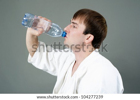 young athlete drinks water