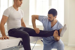 Young athlete getting professional help after sports injury. Serious doctor examining sportsman's knee joint to assign therapy. Physiotherapist and patient using medical exercise to relieve pain