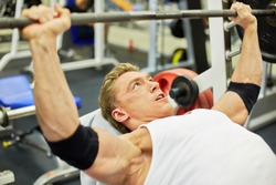 Young athlete man does bench press from chest exercise in gym hall