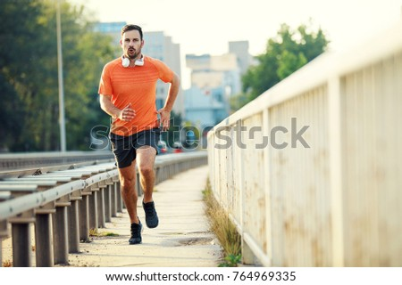 Young athlete man is exercising outdoors. Living healthy lifestyle.  #764969335