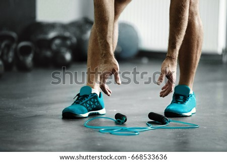 Young athlete man is ready for exercise with rope #668533636