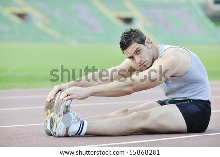 young athlete man relax and strech ready for run  at athletics race track on stadium
