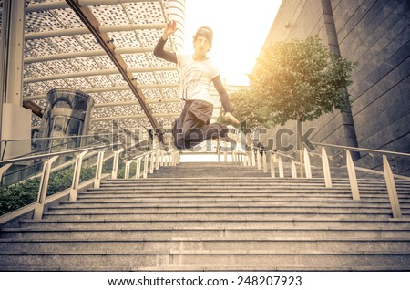 Young athlete performing parkour tricks - Free runner jumping a stairway