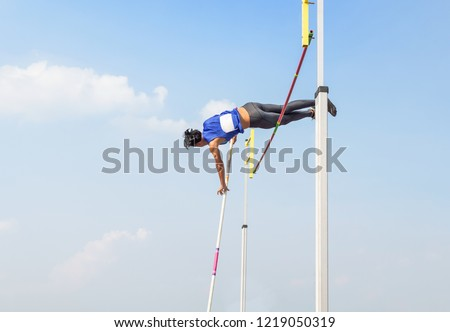 young athlete pole vault pole jumping competition over bar in to the sky at stadium #1219050319