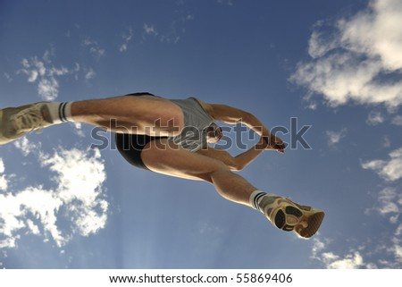 young athlete run and jump height with blue sky and clouds in backgrond