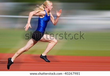Young athlete running down the track with motion blur added - stock photo